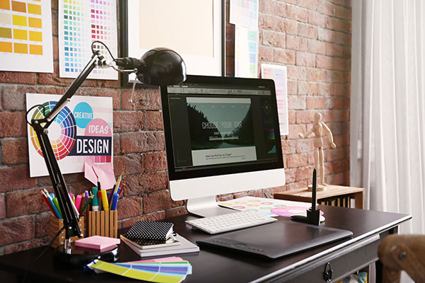 Image of a graphic designer's workspace including a computer and graphics tablet.